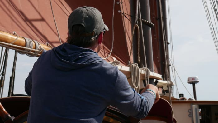 From the helm Dennis monitors the trim on  Angelique's distinctive tanbark sails