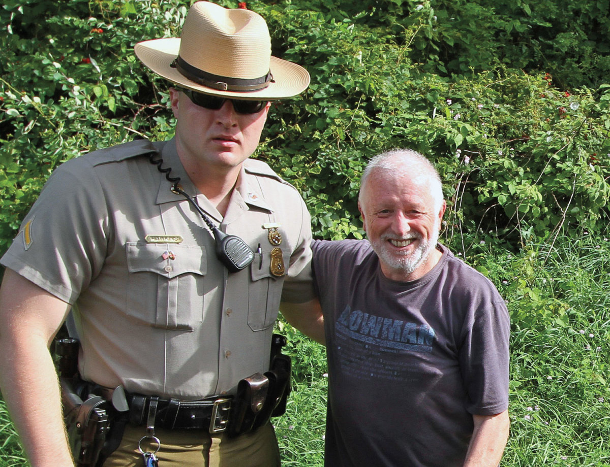 The author, after shredding a trailer tire, is dwarfed by a state trooper in Maryland