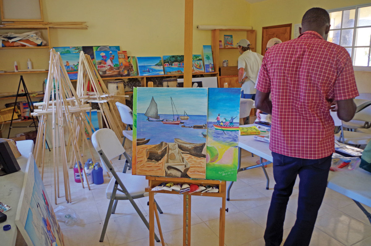 The community center on Isle a Vache receives supplies from the Charlotte crew, here we can see the paintings of local artists that depict life on the island and the traditions the people hope to maintain. Photo Courtesy of Chris Museler
