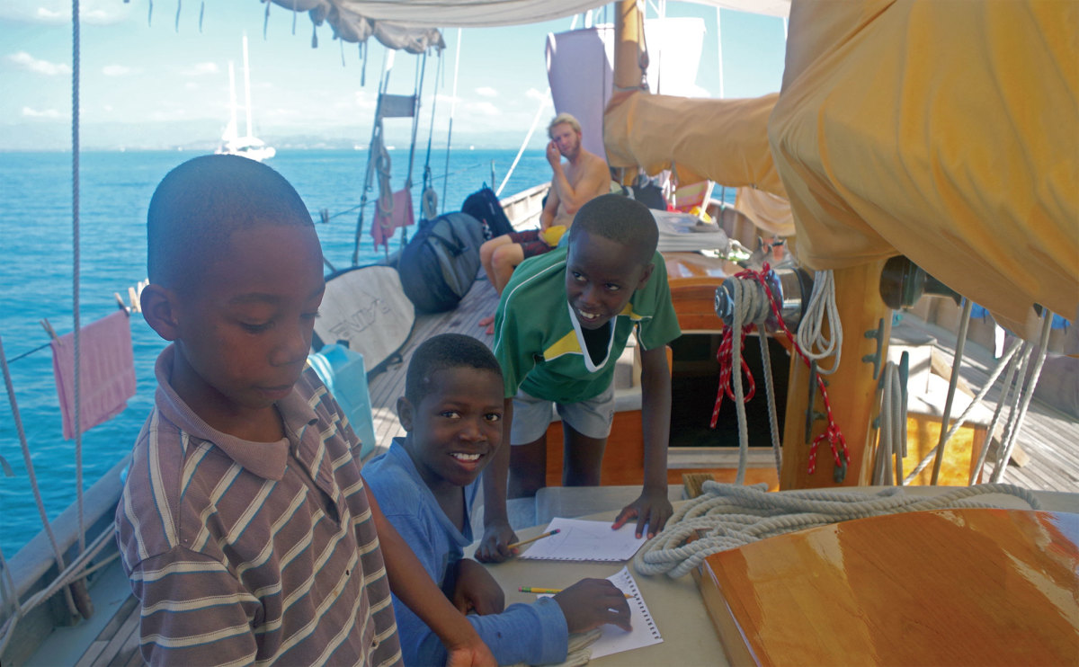 Young Haitian children get a drawing lesson and draft their own schooners aboard Charlotte. Photo courtesy of Chris Museler
