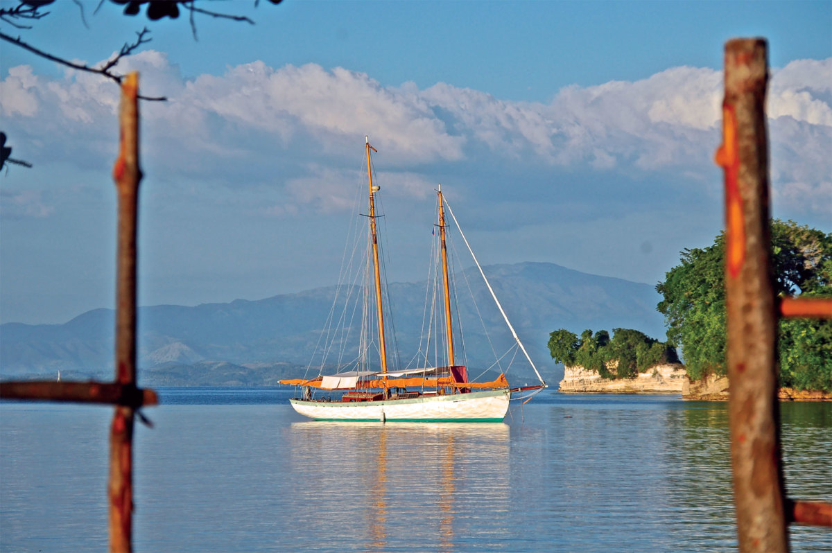 The schooner Charlotte is framed by mainland Haiti's green mountains as she rests for a month in the quiet harbor at Port Morgan, Isle a Vache. Photo by Ian Ridgeway