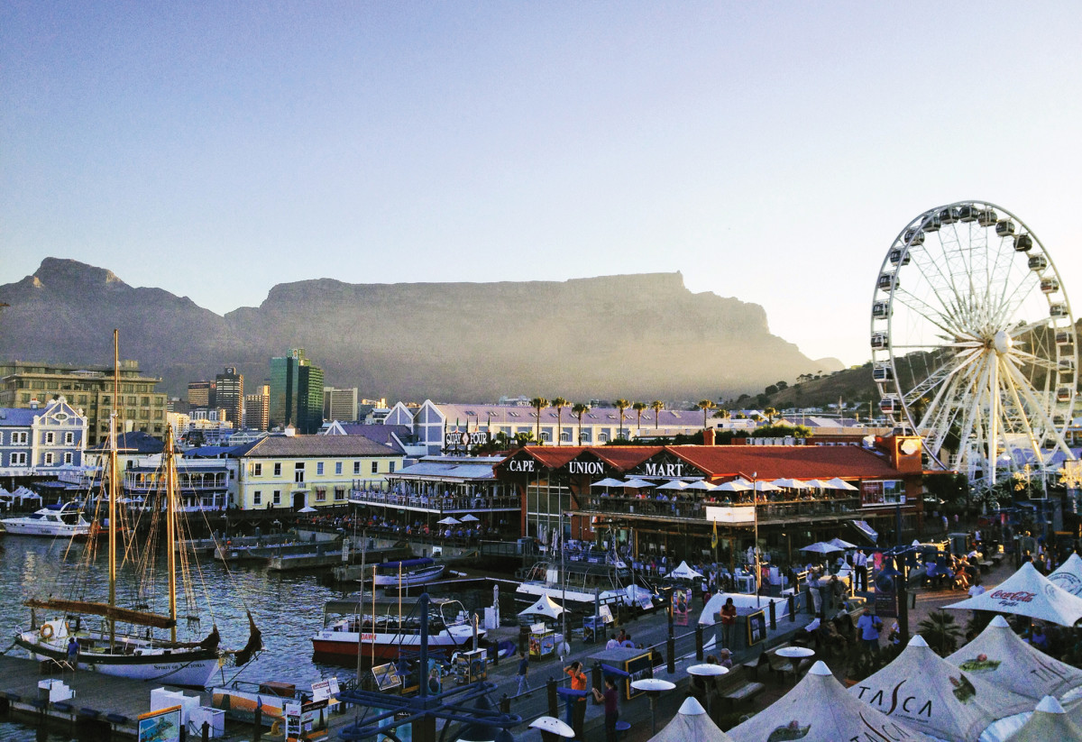 Table Mountain sits in the distance as the Cape Town waterfront bustles with activity