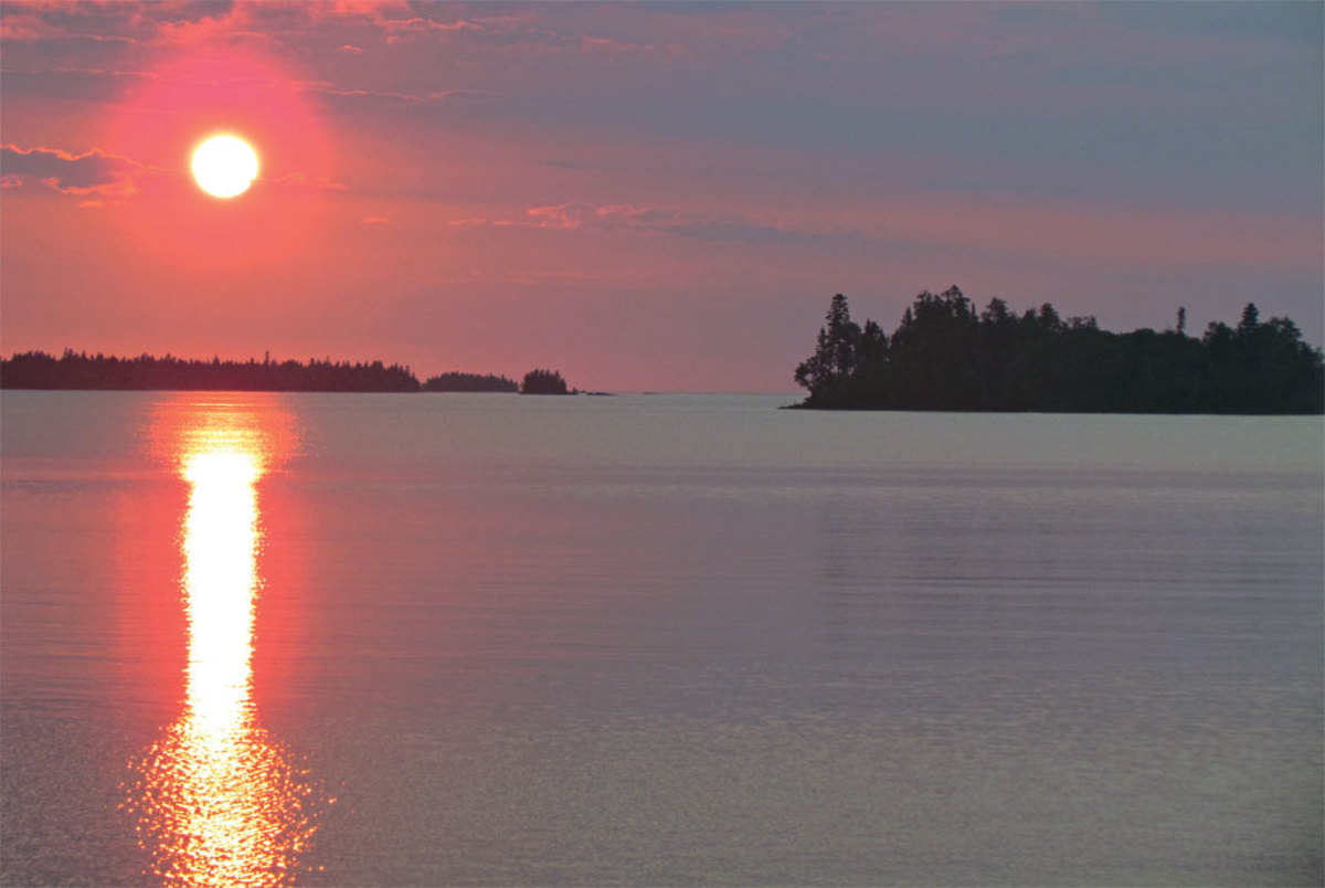 The sun rises over the calm waters of Siskiwit Bay