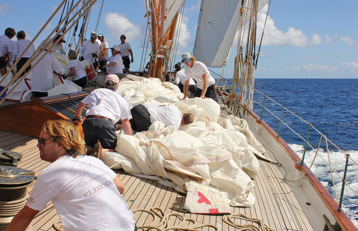The crew prepares to hoist a deck-load of sail as the wind falls light