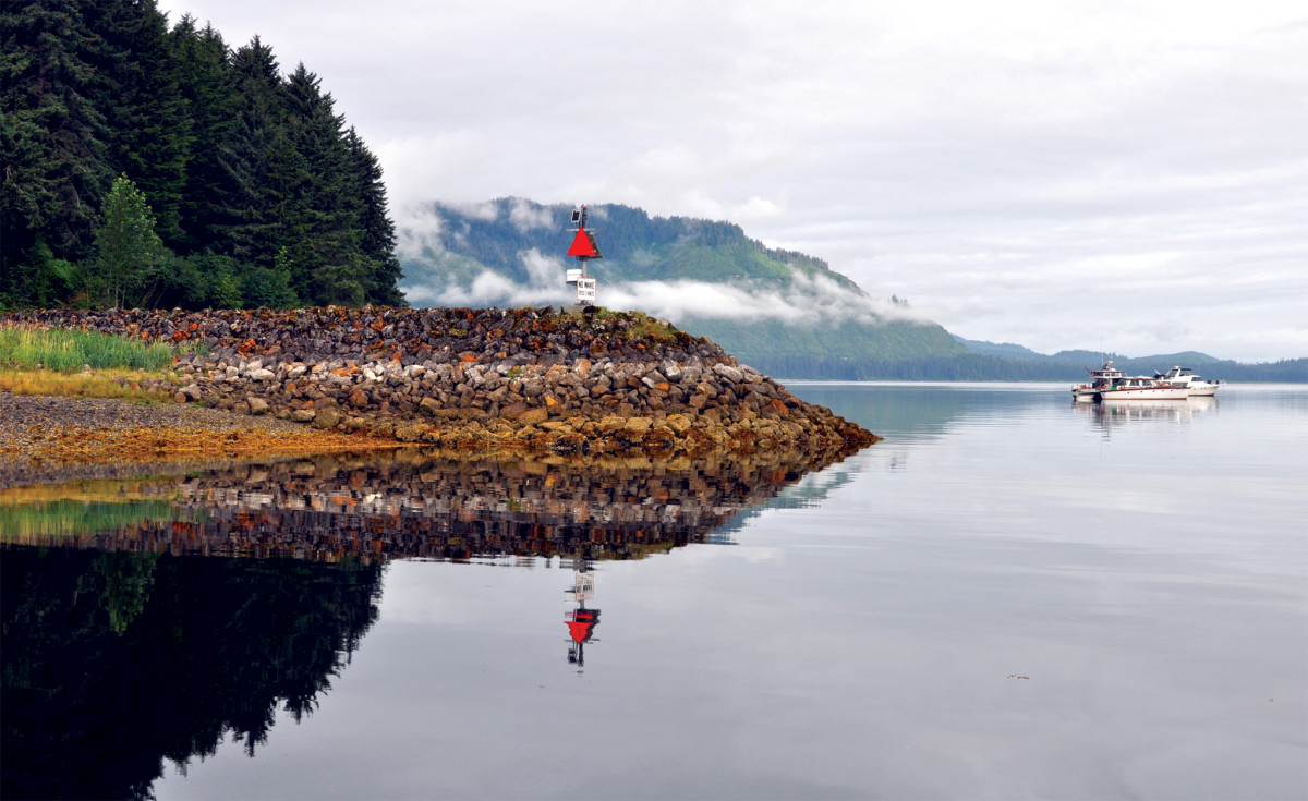 A navigation light marks the breakwater at Hoonah on a windless, misty morning