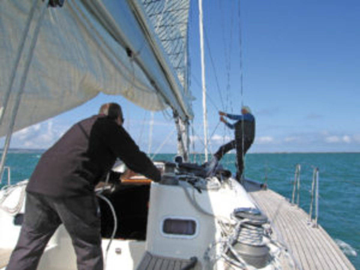 The author uses his weight to heave up the halyard, while another crewmember uses a winch aft to take up the slack