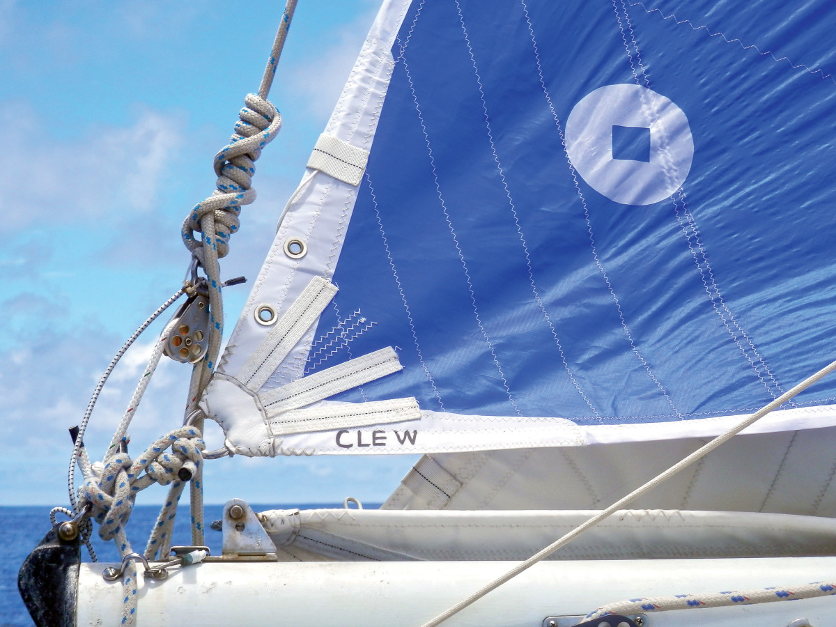 The nylon sail is lashed down at the clew and secured to a reef hook at the tack