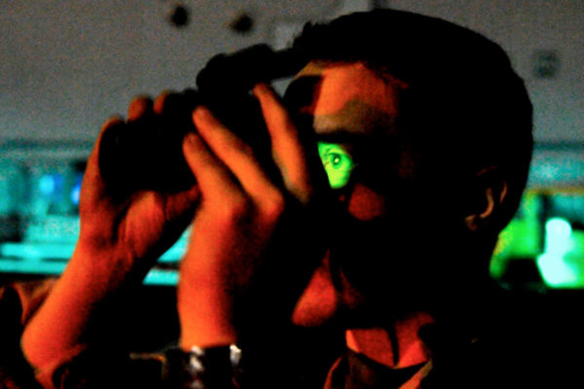U.S. Navy Petty Officer 2nd Class Jordan Lochmann uses night vision binoculars to scan the horizon for Tomahawk missile trails from the flight deck of amphibious assault ship USS Kearsarge during strike missions supporting Operation Odyssey Dawn in the Mediterranean Sea, March 19, 2011.