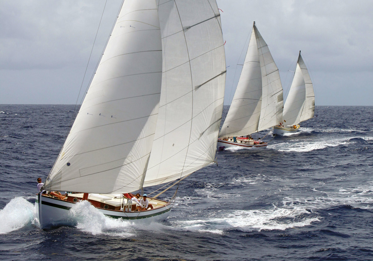 The sloop Genesis leads a trio of traditional workboats on a reaching leg
