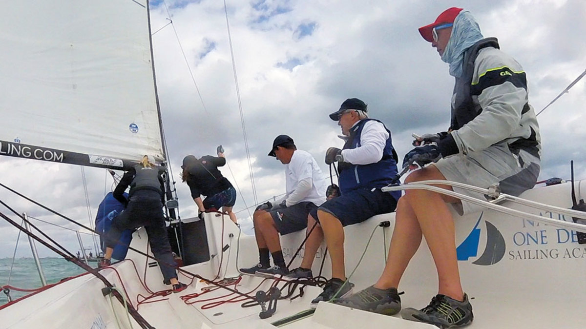 Sabine (at far left) and the author prepare to hoist the spinnaker while Eric takes his turn at the helm