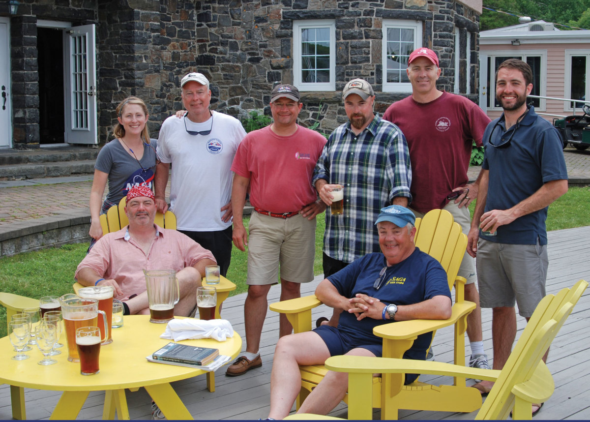 "The crew of Saga (standing from left) Amanda, ""Homeless"" Jon, Brian, Davy, the author and Jason (sitting from left) John McMahon and the skipper, all enjoy a round of beer after the finish"