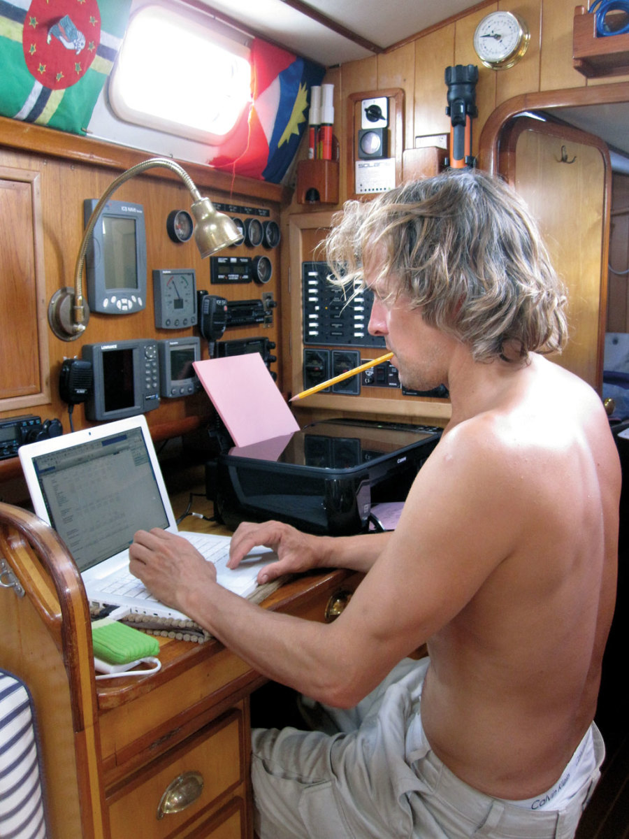 The author's husband gets caught up on work in the nav station