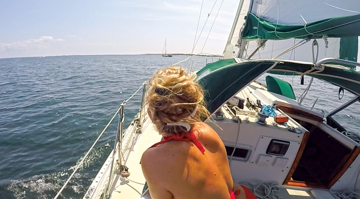 The author watches another local sailboat from the cockpit of her own boat