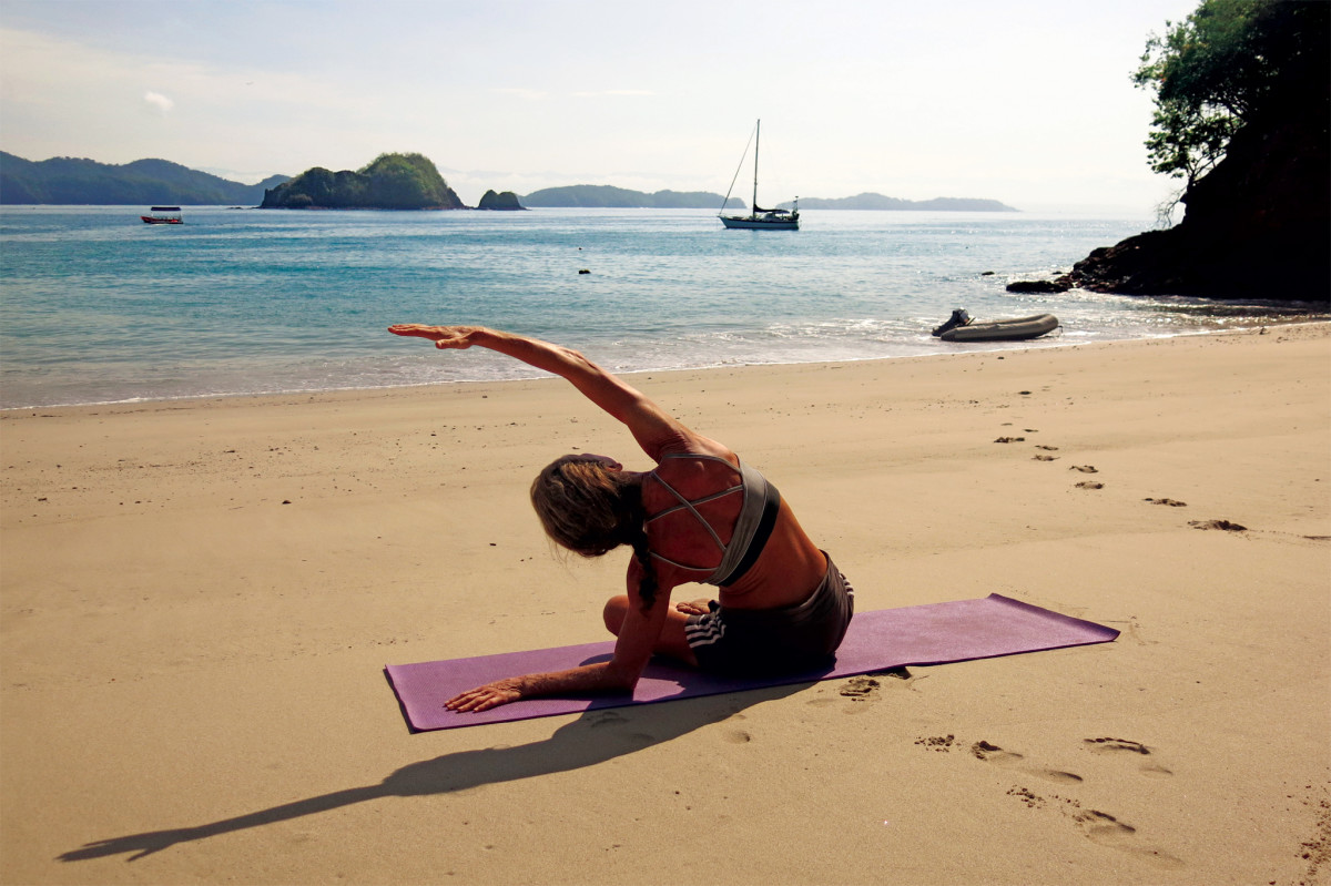 Suzy practices some yoga on a deserted beach with Distant Drummer anchored just offshore