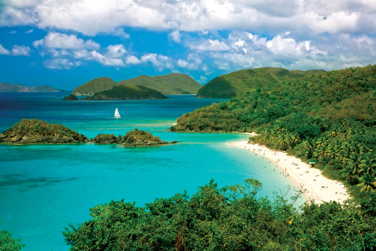 A solitary sailboat glides past Trunk Bay on St John