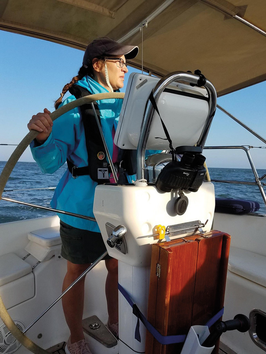 The author's wife, Marjorie, at the helm offshore