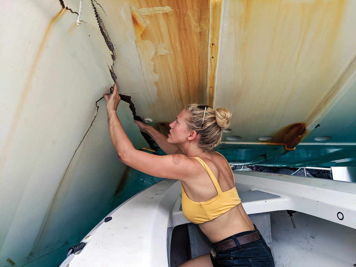 Kimmi examines where the starboard hull became separated from the boat's central structure