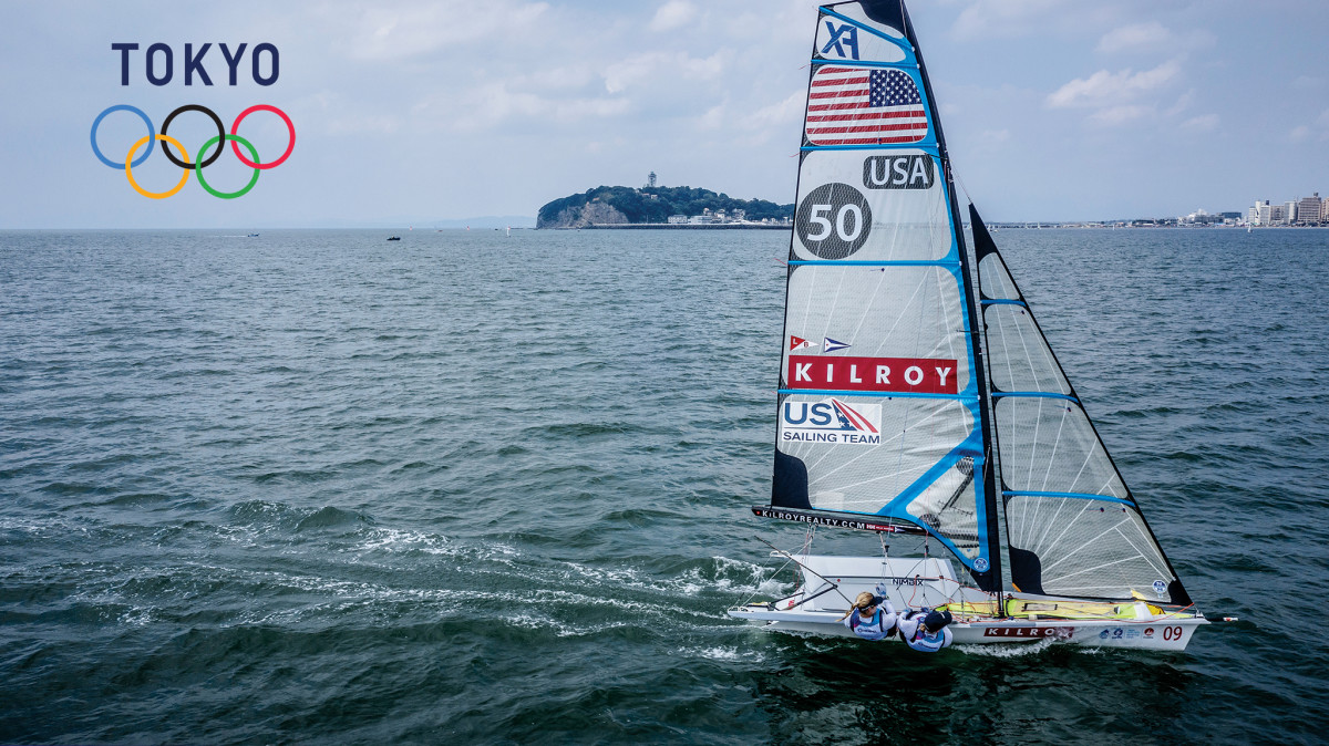 U.S. 49er FX sailors Stephanie Roble (at the helm) and Maggie Shea fine tune their boatspeed on Sagami Bay; note Enoshima Yacht Harbor in the background astern